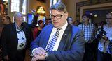 Perussuomalaisten puheenjohtaja Timo Soini vilkuilee kelloa ja työmies Matti Putkonen viittilöi vasemmalla puolueen eduskuntavaalien vaalivalvojaisissa Bottalla Helsingissä.