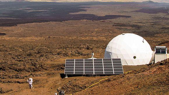 Valkoinen pyöreä rakennus ja avaruuspukuun pukeutunut henkilö suuren aavikon laidalla.