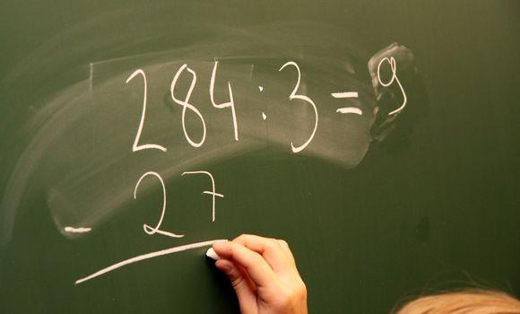 Ala-asteen oppilas laskee matematiikan tehtävää.