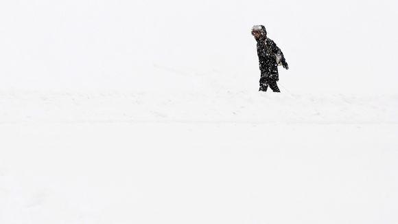 Nainen kävelee lumihangessa.