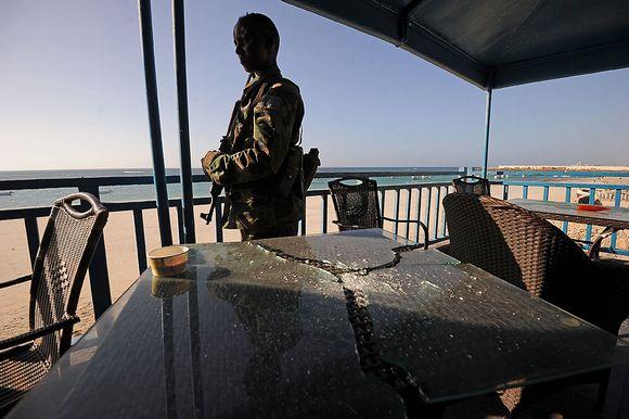 Somalialainen sotilas katselee iltaöisen hyökkäyksen aiheuttamia vahinkoja Liidon rantaravintolassa Somalian Mogadishussa perjantaiaamuna 22. tammikuuta.
