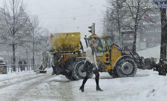 Lumitraktori työssään sankassa lumisateessa Helsingin Mannerheimintiellä.