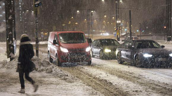 Jalankulkija ja autoja lumisateisessa Helsingissä.