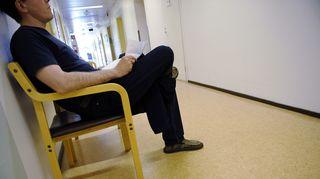 Potilas jonottaa terveysaseman käytävällä.