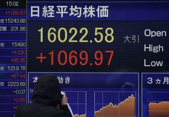 Mies valokuvaa näyttötaulua, jossa näkyy Tokion pörssikursseja maanantaipäivältä 15. helmikuuta.