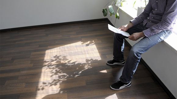 Mieshenkilö tutkii paperia tyhjältä vaikuttavassa asunnossa.