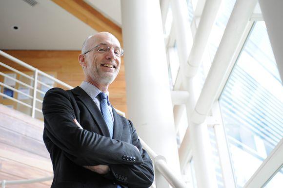 Professori Stuart Parkin kuvattuna avaraa toimistomaisemaa vasten.