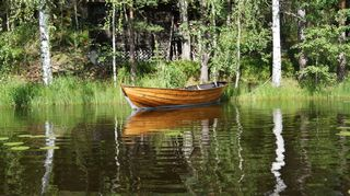 A wooden rowboat at a summer cottage