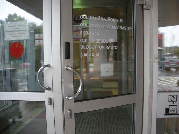 Oulun käräjäoikeuden ja syyttäjänviraston ulko-ovi hivenen avoinna.