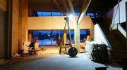 Hirsikoulun pääaulassa työt ovat vielä käynnissä. Vielä suojien peittämissä portaiden kaiteisssa kuviointina on Iijoen profiilista tehty kaiverrus.