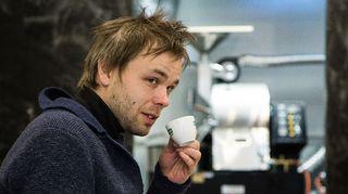 Ville Ranta juo kahvia kahvilassa.