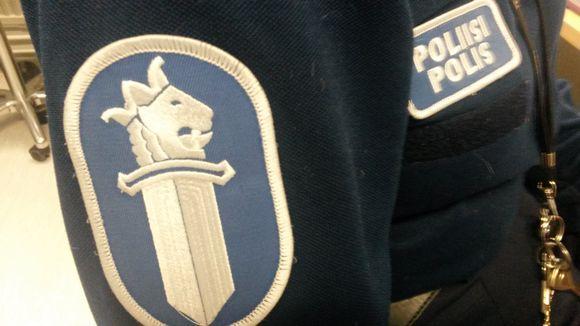 Poliisin sininen virka-asu, jossa hihamerkki ja poliisiteksti.