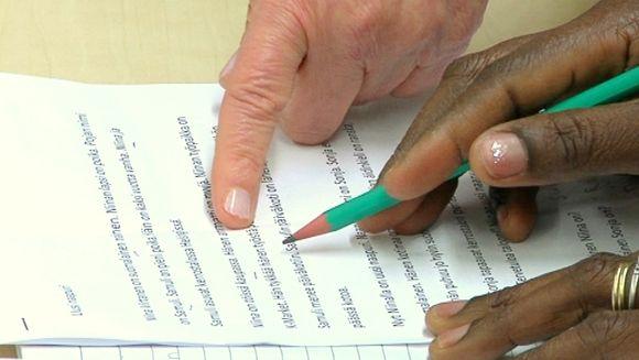 Maahanmuuttaja opettelee lukemaan ja kirjoittamaan