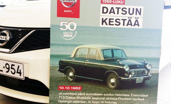 Datsun Bluebird juliste uuden Nissanin edessä.