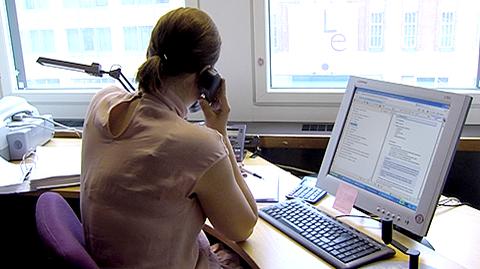 Nainen puhelimessa tietokoneensa ääressä.