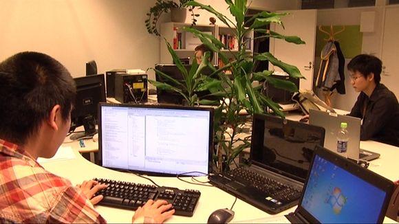 Kaksi kiinalaismiestä tietokoneiden ääressä töissä.