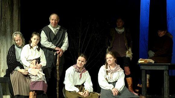Näyttelijät istumassa lavan reunalla