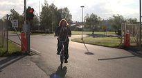 Mies ajaa polkupyörällä ulos tehtaan portista