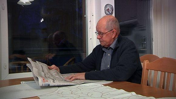 Lasse Vuorenmaa lukee lehteä keittiön pöydän ääressä.