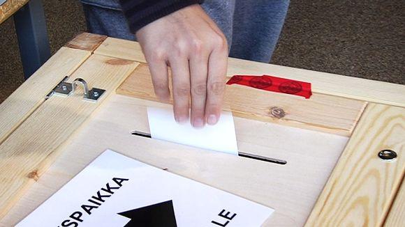 Äänestäjä tiputtaa vaalilipuketta uurnaan äänestyspaikalla.