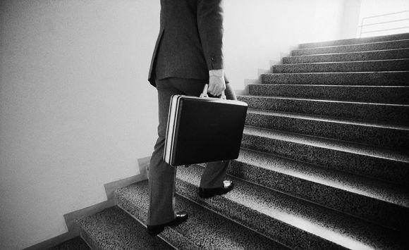 Mies nousee portaita salkku kädessä.