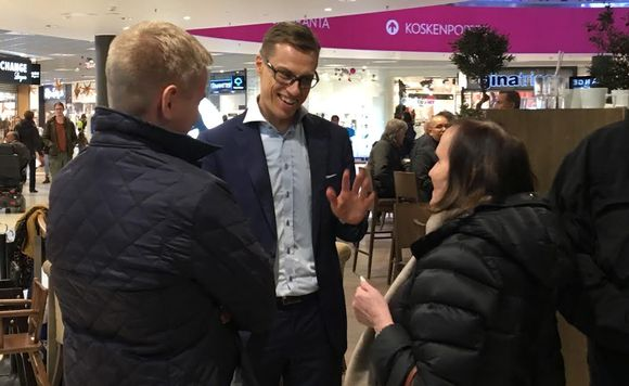Alexander Stubb puhuu ihmisten kanssa märässä paidassa