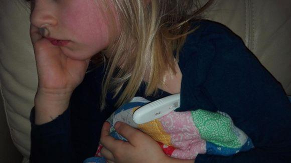 Punaposkinen tyttö kuumemittari ja pehmolelu kainaloissa.