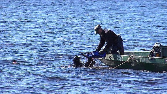 Sukeltajat etsivät räjähteitä järvestä.