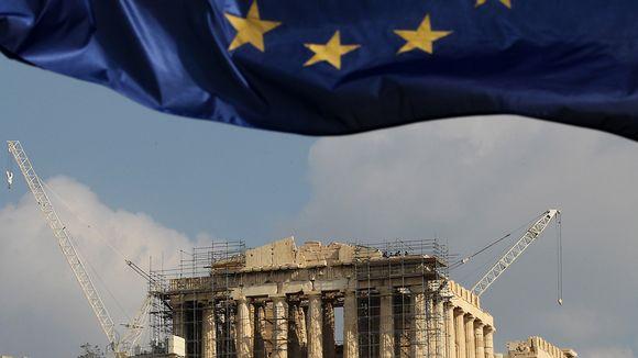 EU:n lippu liehuu edustalla ylhäällä, kaukana takana siintävät Akropoliksen rauniot, joiden ympärillä on rakennustelineitä.