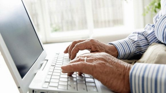 Vanhuksen kädet tietokoneen näppäimistöllä.