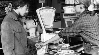 Nuori asiakas kaupan kassalla maksamassa, myyjä lyö ostoksia kassakoneeseen. Vuodelta 1965.