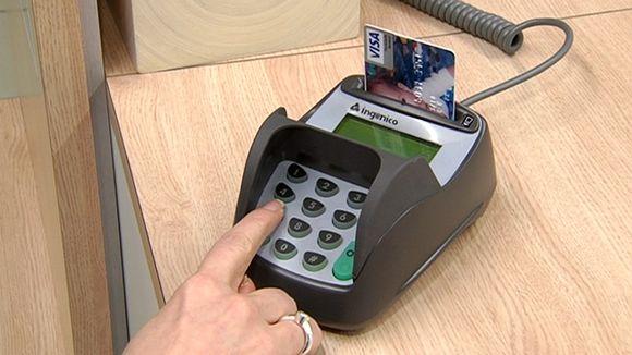 Henkilö maksamassa luottokortilla kaupan kassalla.