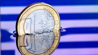 Euron kolikko vedessä, jonka pinnasta heijastuu kreikan lippu.