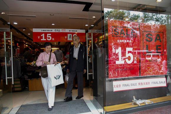 Iäkäs pariskunta muovikasseineen tulee ulos myymälästä, jonka ikkunassa punaiset julisteet kertovat alennusmyynnistä.