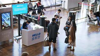 Kiinalaisturisteja opastustiskillä lentokentällä.