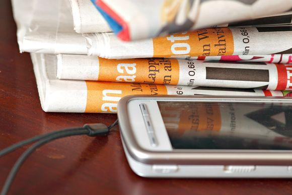 Sanomalehtiä, kännykkä.