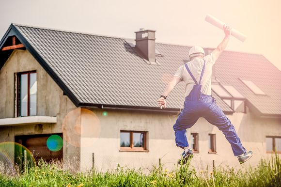 Rakennusmies hyppii piirustukset kourassaan.