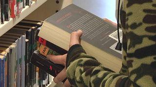 Kirjapino naisen kädessä kirjastossa.