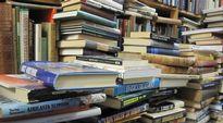 Vanhoja kirjoja hyllyssä ja pinoissa