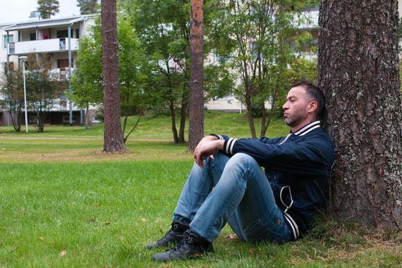 Turvapaikanhakija istuu nurmikolla ja nojaa puuhun.