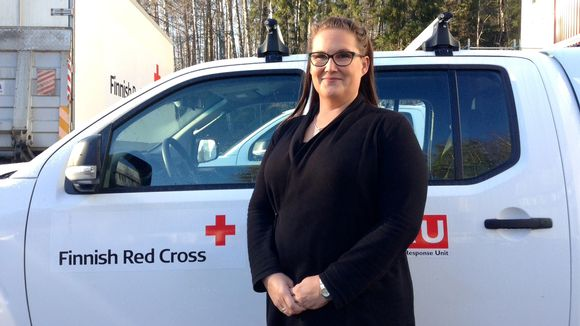 Sairaanhoitaja Virpi Teinilä seisoo Punaisen Ristin logoilla varustetun auton edessä Tampereen Kalkussa.