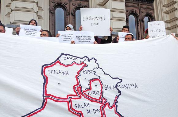 Irakin kartta lakanaan piirrettynä ja mielenosoittajia Keskustorilla.