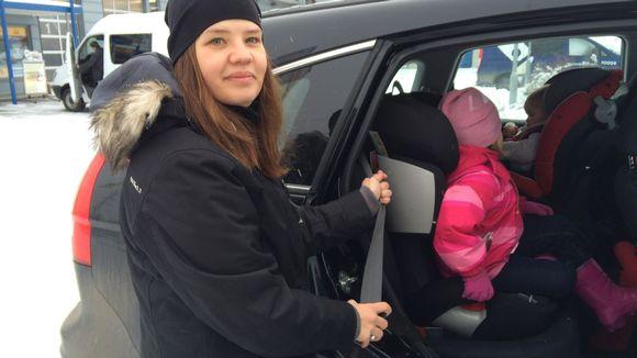 nuori nainen laittaa lapsia autoon