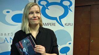 Kati Närhi seisoo palkitsemistilaisuudessa kirja kädessään.