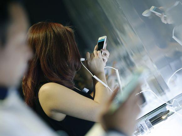 Nainen kokeilee uutta Samsung Galaxy Note 4 -puhelinta Bangkokin messuilla 13. lokakuuta 2014.