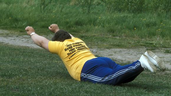 Ylipainoinen mies tekee kuntoiluliikkeitä nurmikolla