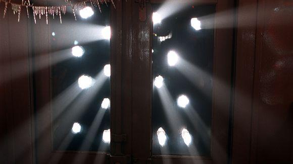 Reikäisestä ikkunaluukusta valo tunkeutuu huoneeseen.
