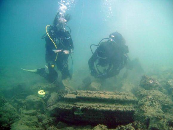 Kaksi sukeltajaa tutkii kivimuodostelmaa.
