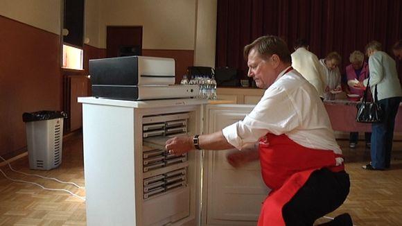 Menumatikin toimitusjohtaja Jukka Penttinen näyttää pakastimesta otetaan ruoka ja laitetaan pakastimen päällä olevaan kiertoilmauuniin.