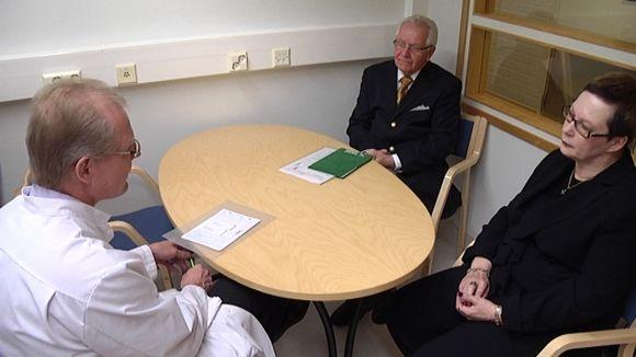 Lääkäri keskustelee pöydän ääressä kahden henkilön kanssa.